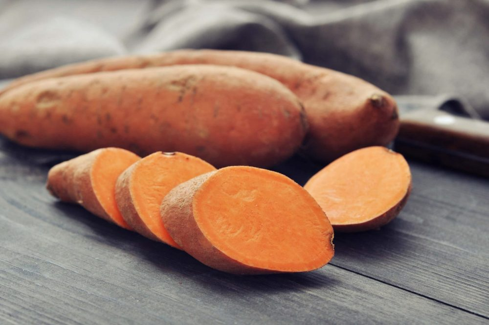 sweet potatoes on a table to show the benefits of sweet potatoes